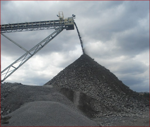 At the end of the conveyor belt, rock drops off into a pile, so that it can begin the process of being sifted through a series of screens. It falls through the screen holes to separate out larger pieces.