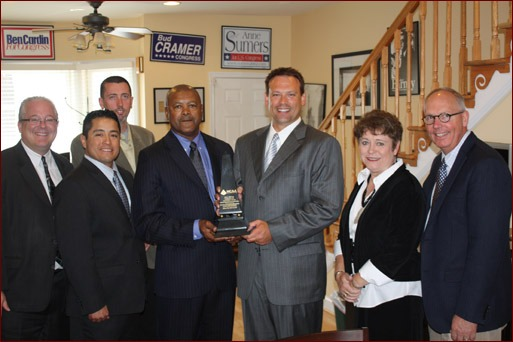 Congressman Heath Shuler accepts the Freedom and Prosperity Award. Shown are Jeff Buczkiewicz, Moroni Mejia, Paul Oldham (rear), Calvin Brodie, Heath Shuler, and Sue and Paul Odom