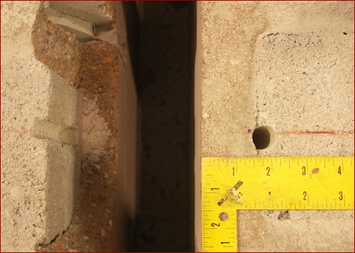 Top of grout-filled concrete masonry wall close-edge distance. Right: Anchor hole before installation and testing. Left: After testing, face of block wall is detached from grout.