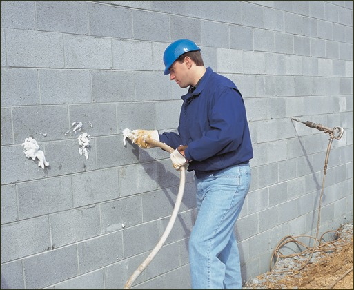 A wall is being filled with CMU foam using the side fill method by drilling 5/8-inch holes.