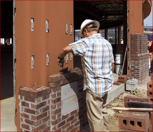 A mason lays brick over a Densglass structural wall coated with a red, fluid-applied air and water barrier. Mason contractors are discovering the benefits of installing air barriers themselves, rather than subbing it out.