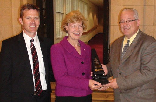 Jeff Buczkiewicz, MCAA President (r) presents Tammy Baldwin (D-WI) with the Freedom and Prosperity Award. Shown left is Joe Buechel,  Natural Stone Veneers International.
