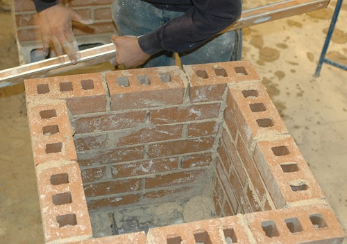 A Kirkwood Masonry student's hands rapidly work a brick tower during the SkillsUSA competitions at Jones Hall in April 2013.