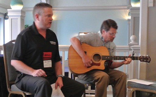 Greg Althammer (left) from Airplaco (MCAA Strategic Partner) performs a song during the MCAA Board Meeting with Jeff Leonard (right) from QUIKRETE (MCAA Strategic Partner) on guitar.