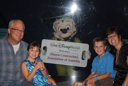 MCAA President and CEO Jeff Buczkiewicz (left) with daughter Logan, son Blake, wife Tami (right), and Mickey Mouse (center) during the MCAA Closing dinner at the Living Seas Salon at Epcot.