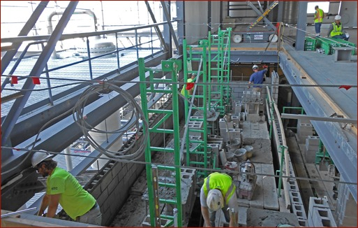 Photo 1:  Seedorff Masonry used Non-Stop scaffolding in a 90-foot-high elevator shaft. The masons outriggers and Inside Corner Arms were used to fully plank the inside of the shaft.