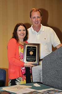 Ashlee Koontz Moore receives the Safety Award plaque on behalf of Koontz Masonry in Lexington from TriSure Corp.'s John Cramer, chairman of the NCMCA Safety Committee.