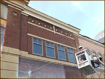 A technician from Sparklewash Construction Services, Omaha, Neb., cleans a mixed masonry facade.