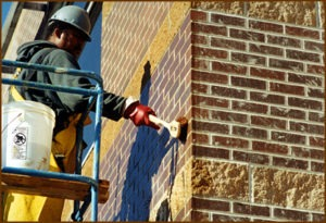 A worker gently scrubs a masonry wall. Gentle scrubbing is usually all that's needed if you're cleaning correctly. The masonry cleaner should do most of the work of dissolving contaminants.