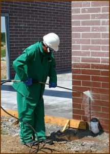 A technician cleans concrete brick. Note that the cleaning procedure for masonry starts at the bottom and works up. This is to keep rundown from soaking into, and staining dry masonry. Masonry below the area being cleaned always needs to be kept wet so that rundown won't soak in.