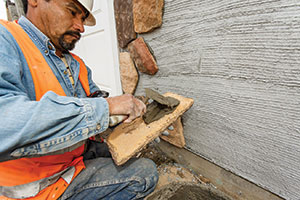"Shown in this picture is the placing of mortar by ""buttering"" the back of the adhered masonry veneer unit."