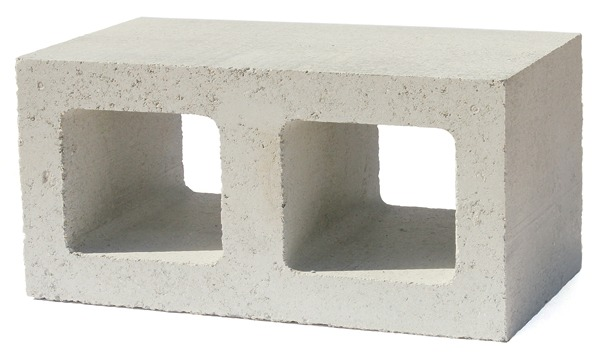 """Interior fireplace made of Watershed Block, a new type of structural masonry that uses less cement and incorporates unwashed, locally sourced recycled aggregate. These block were manufactured using a combination of two different regionally sourced aggregates. Varying the ratio between the two in the formulation resulted in the """"random mottling"""" that gives the walls their natural appearance. The architects wisely use the block to encase the wood stove to serve as a heat sink – a thermal flywheel. Image credit: ©Ed Caldwell"""