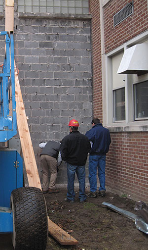 Figure 3. Bert Sherman, Scott Walkowicz and Scott Wilmot examining the masonry structure. The poor condition of the masonry was not noticeable before the demolition started, but once the brick veneer was removed, the defects were readily apparent.