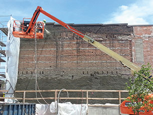Western Specialty Contractors worker sprays shotcrete on the entire west elevation of the historic Norden Hall building repurposed as a wine bar in Des Moines, Iowa. Once the new concrete had cured, a textured acrylic coating was applied to waterproof the wall and maintain its historic appearance.